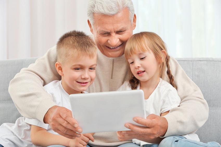 Großvater mit Enkeln benutzen Tablet