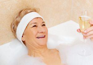 Gut gelaunte Seniorin mit Sekt in Badewanne