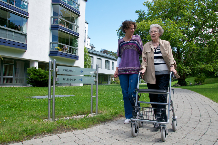 Seniorin mit Rollator vor Pflegeheim