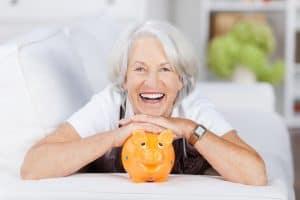 Lachende Seniorin mit Sparschwein
