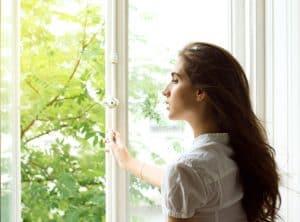 Junge Frau an offenem Fenster