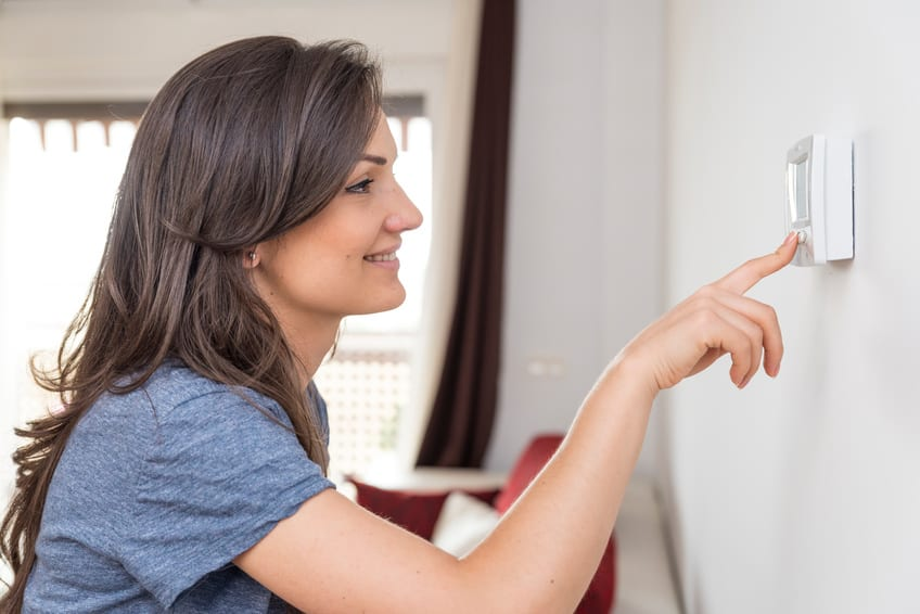 Frau regelt Thermostat