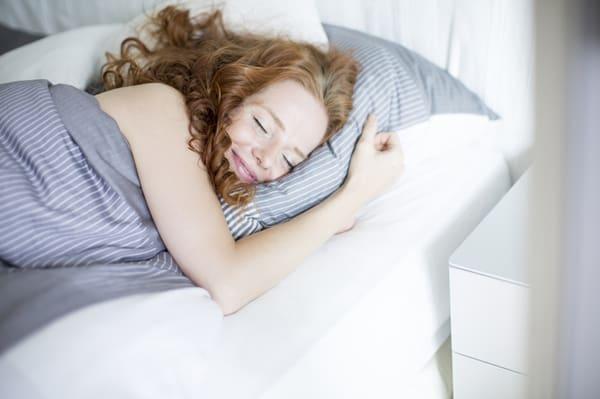 Lächelnde junge Frau im Bett