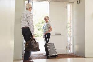 Seniorenpaar mit Koffern verlassen Wohnung