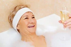 Gute gelaunte Senioren mit Sekt in Badewanne